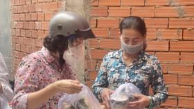 Chủ tịch Ủy ban MTTQ Việt Nam TPHCM Tô Thị Bích Châu trao tặng bánh chưng, chả lụa của đồng bào các dân tộc tỉnh Hà Giang đến các thợ hồ tại  1 công trình xây dựng trong hẻm 518 Lê Văn Sỹ