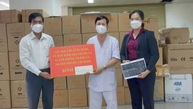 Phó Trưởng Ban Dân vận Thành ủy Ngô Văn Luận (bìa trái) trao bảng tượng trưng hỗ trợ y bác sĩ, nhân viên y tế Bệnh viện dã chiến thu dung điều trị Covid-19 số 2. Ảnh: HOÀI NAM