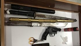 Lực lượng công an thu giữ súng, bình xịt hơi cay cùng nhiều đao kiếm khi khám xét nơi ở của đối tượng