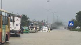 Nước ngập sâu một đoạn gần 100m trên tuyến Quốc lộ 1A tại huyện Phú Ninh (tỉnh Quảng Nam) khiến giao thông gặp khó khăn. Ảnh: NGUYỄN CƯỜNG