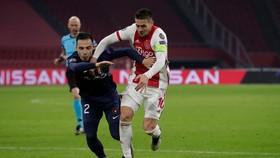 Johan Dion Cools trong pha tranh chấp với Hakim Ziyech tại Champions League