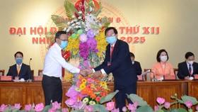 Đồng chí Nguyễn Hữu Hiệp (trái) tặng hoa chúc mừng đại hội