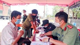 Lực lượng chức năng kiểm tra giấy tờ của người dân tại chốt kiểm soát trên Quốc lộ 1A, TP Cam Ranh. Ảnh: QUỲNH ANH