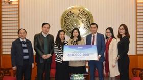 Ông Nguyễn Phương Sơn – Giám đốc Đối ngoại Amway Việt Nam trao biển tượng trưng số tiền tài trợ cho đại diện Báo Điện Tử Chính Phủ