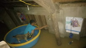 Người dân tại một ngôi nhà ở Quảng Xá, xã Tân Ninh tìm cách thoát lũ