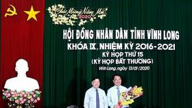 Ông Trần Văn Rón, Bí thư Tỉnh ủy Vĩnh Long (bên trái), tặng hoa chúc mừng ông Lữ Quang Ngời. Ảnh: PHAN THANH