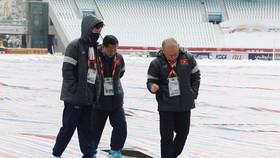 Ông Park Hang-seo cùng các cộng sự đi kiểm tra mặt sân vẫn chưa được tháo bạt . Ảnh: ANH KHOA