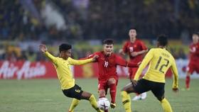 Quang Hải giữa vòng vây của hậu vệ Malaysia. Ảnh: DŨNG PHƯƠNG