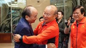 Thủ tướng Nguyễn Xuân Phúc chúc mừng HLV Park Hang-seo tại buổi gặp mặt 2 đội tuyển bóng đá nam và nữ vừa từ Philippines trở về tối 11-12. Ảnh: MINH HOÀNG