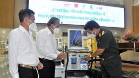 Nguyên Phó Thủ tướng Thường trực Trương Hòa Bình và Thiếu tướng, PGS, TS, TTND Nguyễn Hồng Sơn, Giám đốc Bệnh viện Quân y 175 kiểm tra hệ thống máy thở được trao tặng