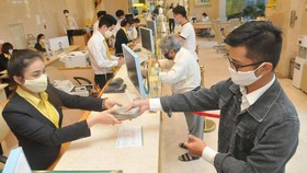 Customers do transactions at a commercial bank in Ho Chi Minh City. (Photo: SGGP)