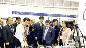 Mr. Nguyen Thanh Phong, Chairman of the Ho Chi Minh City People's Committee, exchanges with domestic enterprises about the capability of supplying supporting industry products for FDI enterprises. (Photo: SGGP)