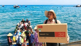 A resident on Nhon Chau Island buys a television to use after the island connects to the national power grid. (Photo: SGGP)