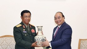 Prime Minister Nguyen Xuan Phuc (R) presents a gift to Sen. Lt. Gen. Suvon Luongbunmi, Deputy Defence Minister and Chief of the General Staff of the Lao People's Army, at their meeting on May 14 (Photo: VNA)