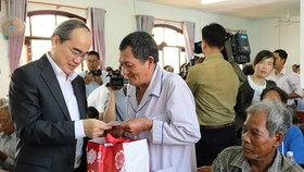 Secretary of HCMC Party Committee Nguyen Thien Nhan presents Tet gifts to local people in Chau Thanh district, Tra Vinh province. (Photo: Sggp)