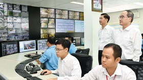 Secretary of HCMC Party Committee Nguyen Thien Nhan  (Standing,R ) visits the Traffic Control and Monitoring Center in HCMC. (Photo: Sggp)