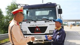 A member of the traffic police checks the paperwork of a truck driver on the Hanoi-Hai Phong Expressway. (Photo: VNA)