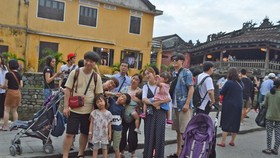 Tourists visit Hoi An ancient town.