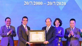 Prime Minister Nguyen Xuan Phuc (third, right) presents a merit certificate to the Ho Chi Minh Stock Exchange at the ceremony on July 20 (Photo: VNA)