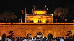 Visitors stand in front of Doan Mon (Main Gate) of the Thang Long Imperial Citadel in the evening (Photo: VNA)