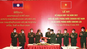 The defence ministers of Vietnam and Laos exchange the signed 2021 cooperation plan in Hanoi on December 4 (Photo: VNA)