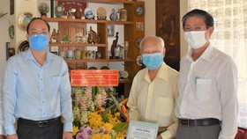 Deputy Secretary of the HCMC Party Committee Nguyen Ho Hai (L) visits Hero of Labor, Pharmacist Tran Van Nhieu. (Photo: SGGP)