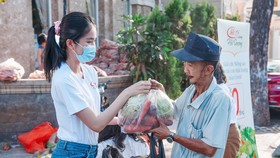 The first runner-up of Miss Vietnam 2020, Pham Ngoc Phuong Anh presents agricultural products to a person. (Photo: SGGP)