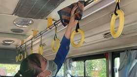 A worker is cleaning and disinfecting a bus. (Photo: SGGP)