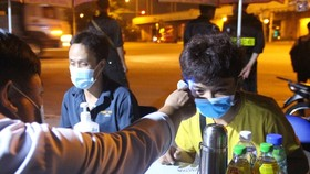 Healthcare workers are measuring the temperature of arrivals at a checkpoint. (Photo: SGGP)
