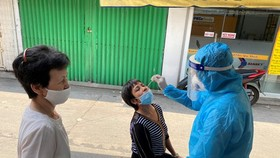 A health worker takes a sample from a woman for Covid-19 test at an area on Cao Thang Street in Phu Nhuan District. (Photo: SGGP)