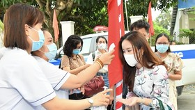 Healthcare workers measure voters' body temperature. (Photo: SGGP)