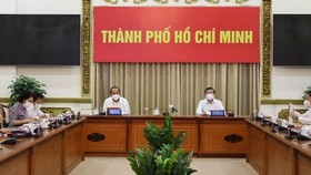 Deputy PM Truong Hoa Binh (L) and Chairman of the HCMC People's Committee Nguyen Thanh Phong  at the meeting ( Photo: SGGP)