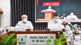 Head of the Propaganda and Education Board of the City Party Committee, Phan Nguyen Nhu Khue (L) and Vice Chairman of the People's Committee Duong Anh Duc attend the virtual press conference  at the HCMC Press Center. (Photo: SGGP)