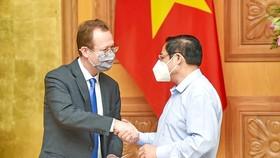 Prime Minister Pham Minh Chinh (R) receives Interim Representative of the US Embassy in Vietnam Christopher Klein. (Photo: SGGP)