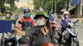 Residents provide health declaration QR Code at the checkpoint on Dinh Bo Linh Street in Binh Thanh District. (Photo: SGGP)