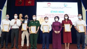 Vice Secretary of the HCMC Party Committee Nguyen Ho Hai (2nd,L) and Chairwoman of the HCMC chapter of Vietnam Fatherland Front To Thi Bich Chau (3rd, R) present letters of thank to donators. (Photo: SGGP)