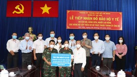 Head of the HCMC Party Committee's Commission for Mass Mobilization Nguyen Huu Hiep (R)  presents gifts to Goa Vap District. (Photo: SGGP)