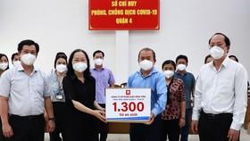 Đồng chí Nguyễn Hồ Hải và đại diện nhà tài trợ trao máy SpO2 cho lãnh đạo quận 4.