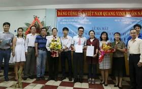 《西貢解放報》共青團書記阮祥欣(左六)和本報編委、編輯部主任范興(右一)遞交成立決定書和贈花祝賀。