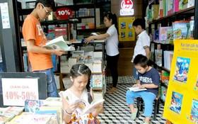 小朋友們在市書香街某一書攤裡看書。(圖源:互聯網)