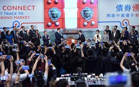 7月3日,在香港交易所,中國人民銀行副行長潘功勝(鑼右側)和香港金融管理局行政總裁陳德霖+(鑼左側)共同為當日首筆交易鳴鑼開市。(資料圖源:王申)