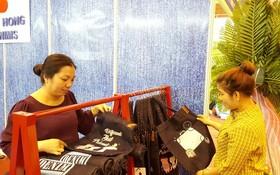 消費者選購華人企業越鴻公司的牛仔布袋。(資料圖源:曉東)