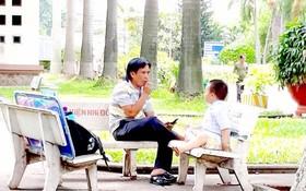 一病童家長在第二兒童醫院庭院裏對著孩子抽煙。
