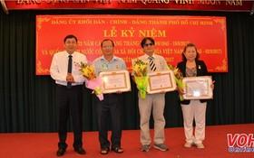 市內政處主任陳世琉(左)向各級黨委代表頒授黨齡紀念章。(圖源:VOH)
