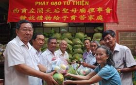 西貢左閭天后聖母廟會長李祺鏢(左一) 與理事們向貧困同胞贈送禮物。