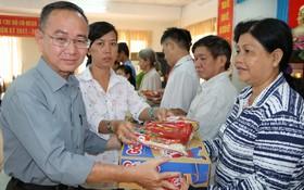 本報編輯部主任范興及工會副主席陳月寶向 平新郡華人贈送禮物。