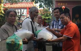 決勝村關聖帝廟理事長楊振明(右一)和副理事 長兼財政陳昶霖(右二)向窮人派發大米。