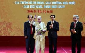 政府副總理武德膽(右二)向人民藝人、教授陳榜贈送鮮花祝賀。(圖源:廷南)