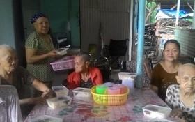 黎氏敬老師向老人們送上晚飯。