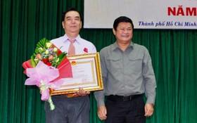 市人委會副主席黃革命(右)向朱杞文同志頒贈三等勞動勳章。